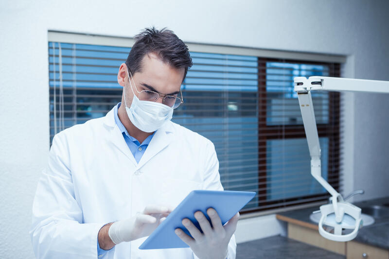 Oral surgeon reviewing patient record on tablet